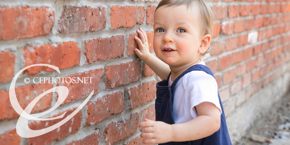 baby boy on red brick wall in overalls denver photographer
